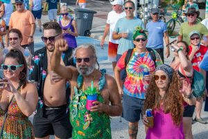 A photo of a group of revelers in colorful shirts at a street festival.