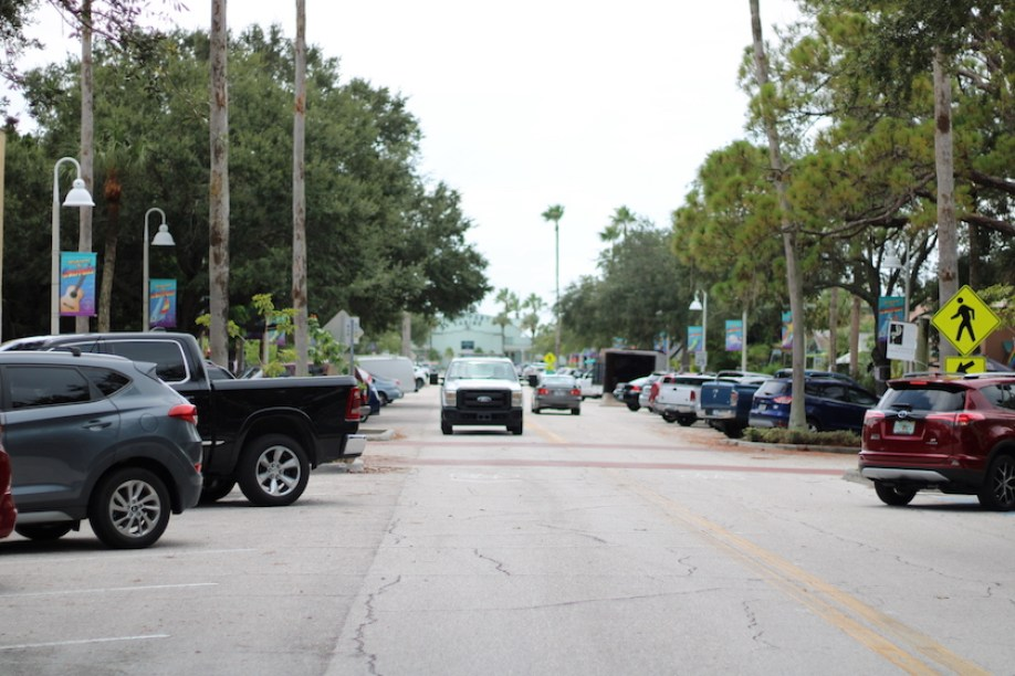 A photo of a road lined with trees with a white truck coming toward the camera and many cars parked diagonally on each side