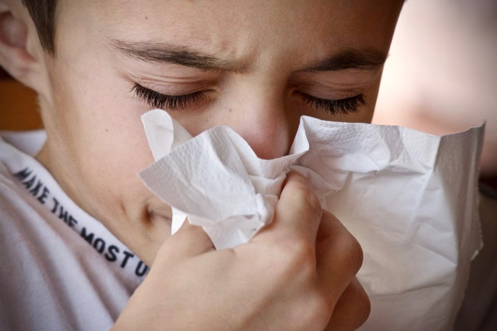 A close up photo of a kid sneezing with a tissue to his nose.