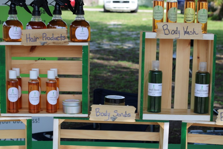 A photo of hair and body products in bottles set in rustic wooden display crates