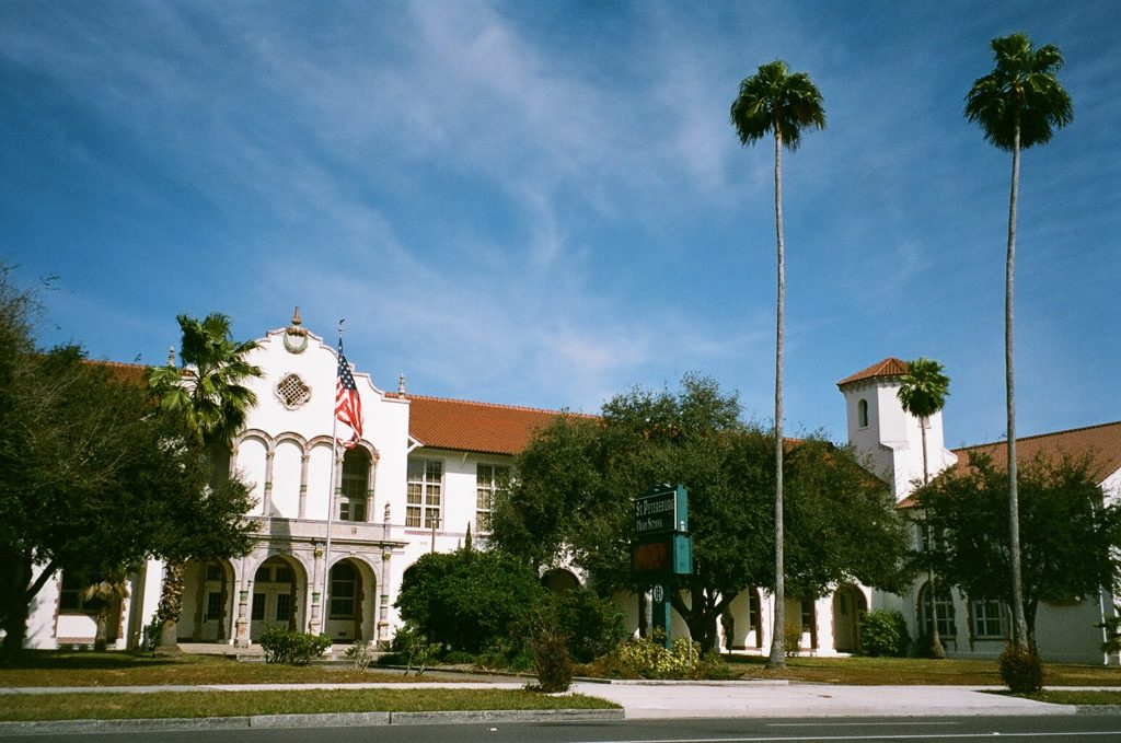 A photo of a Spanish mission style building with palm trees and green lawn.