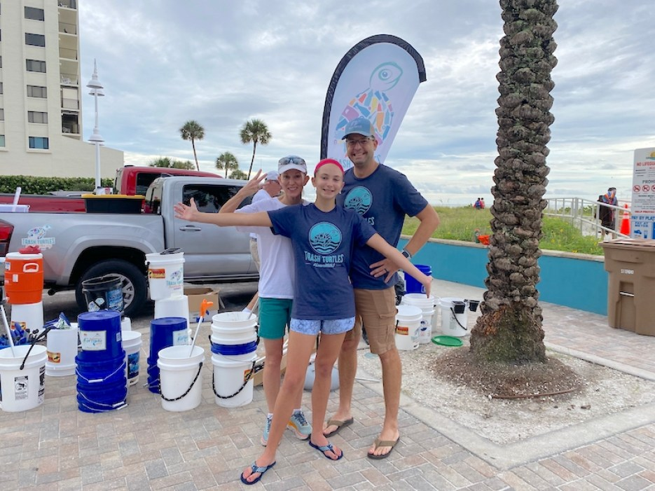 A photo of a young girl with a man and woman in blue t-shirts standing behind her in a beach parking lot next to a collection of buckets.