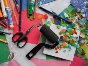 A table full of craft supplies. A glue gun, scissors, markers and colored paper all sprawled out.