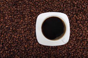 White mug of coffee over brown coffee beans