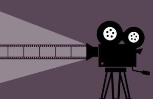 A cartoon image of an old school black camera on a tripod shooting a light of film