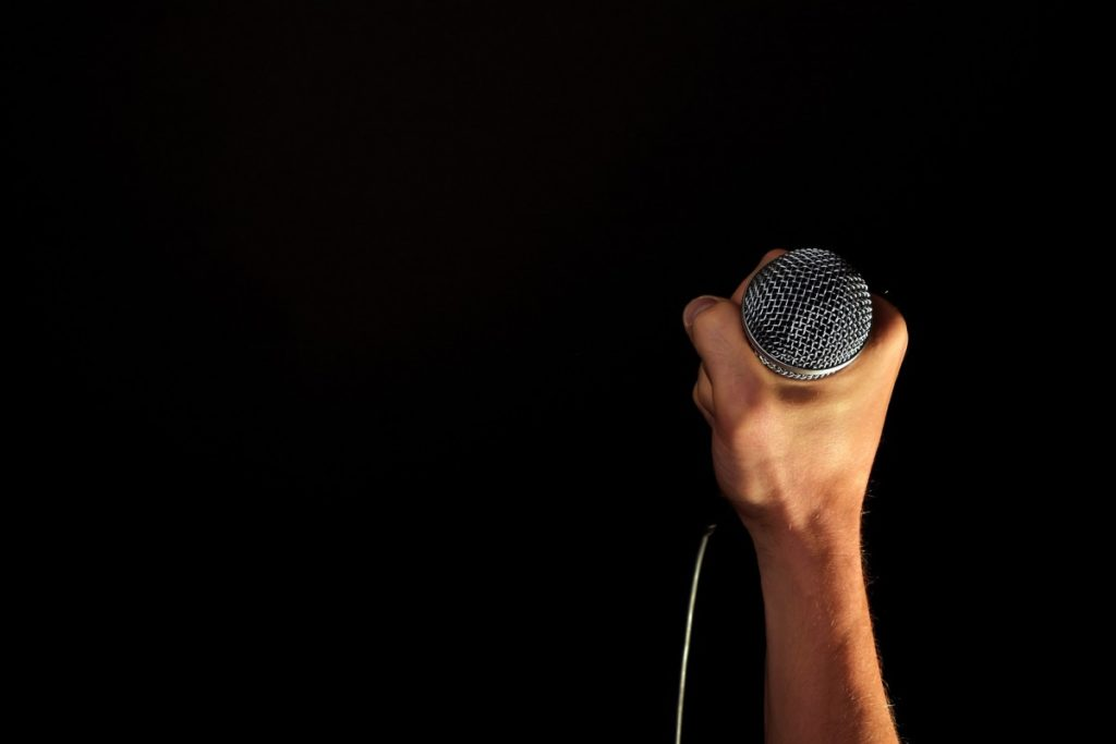 A hand gripping a microphone