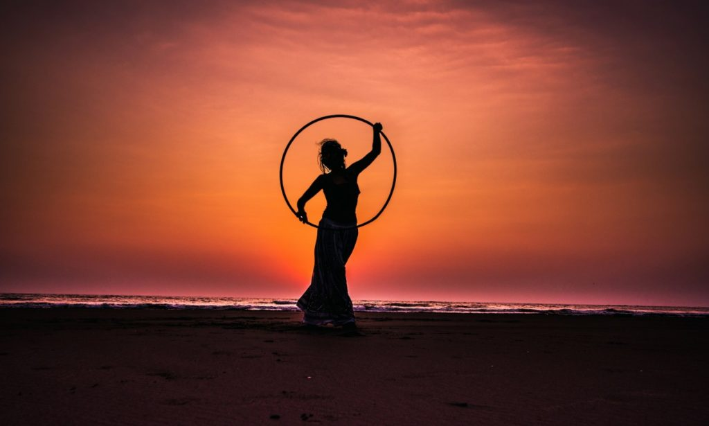 A woman with a hoola hoop standing against a very orange sunset