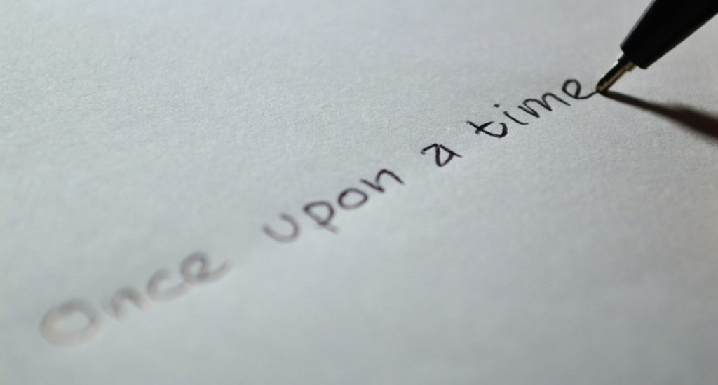 """A marker writing """"Once Upon a Time"""" on a white piece of paper"""