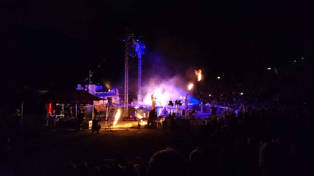 Outdoor concert with flames and lights on a stage