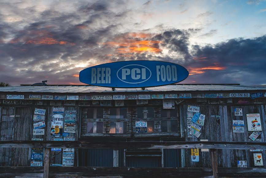 A brown wood building with a blue sign that reads 'PCI' in front of a sunset sky