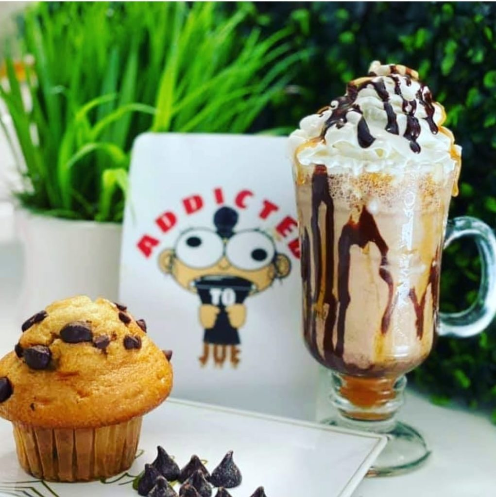 """A photo of an iced coffee drink with whipped cream on a table next to a muffin with a sign in the back that has a cartoon face on it and """"Addicted"""" in red letters."""