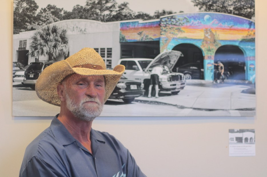 A photo of a man in a straw cowboy hat looking at the camera, standing in front of a large black and white photo with spots of color in it.