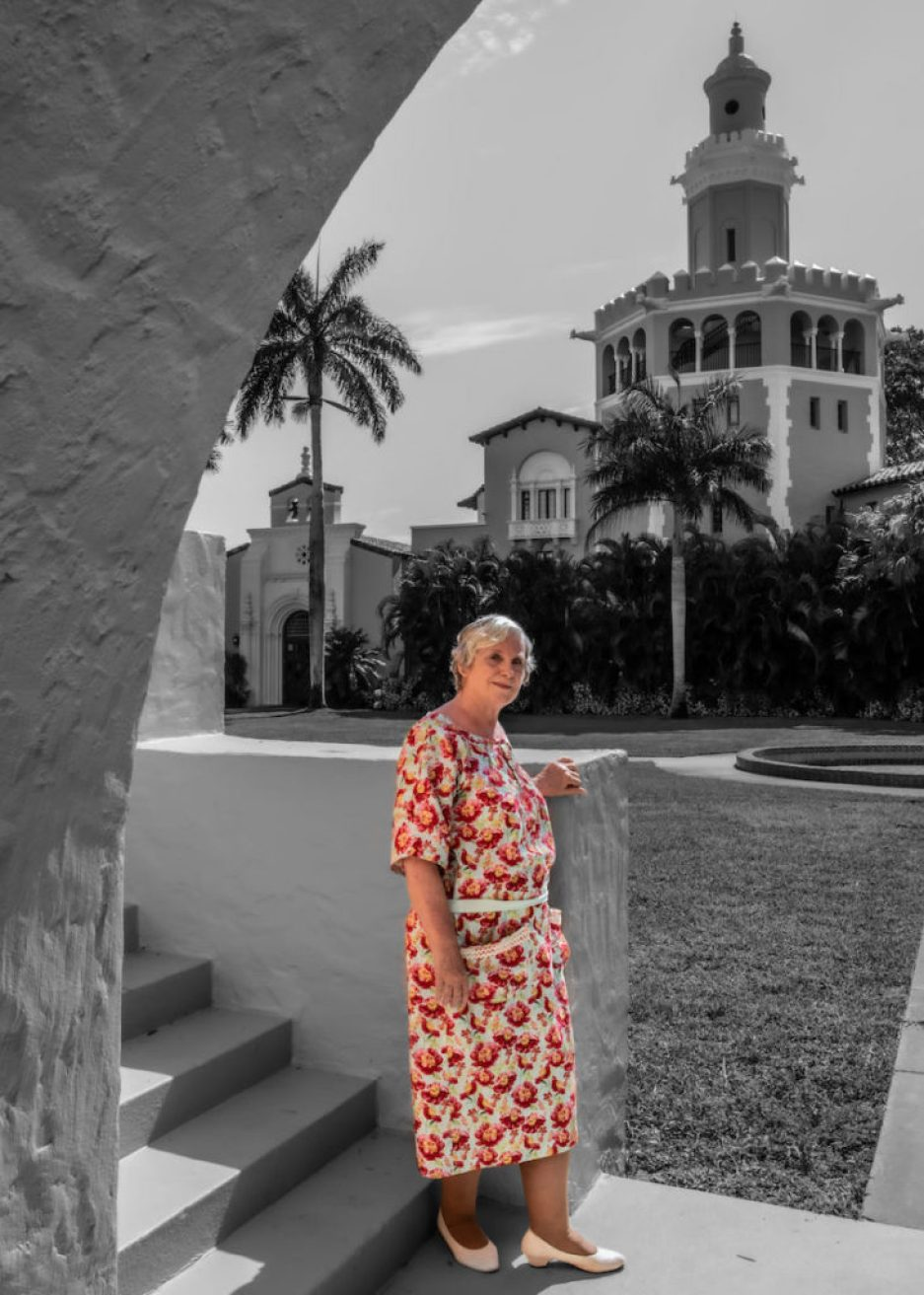A black and white photo of a woman outside a Spanish-style building tower, where the woman and her flowery dress have been colorized.