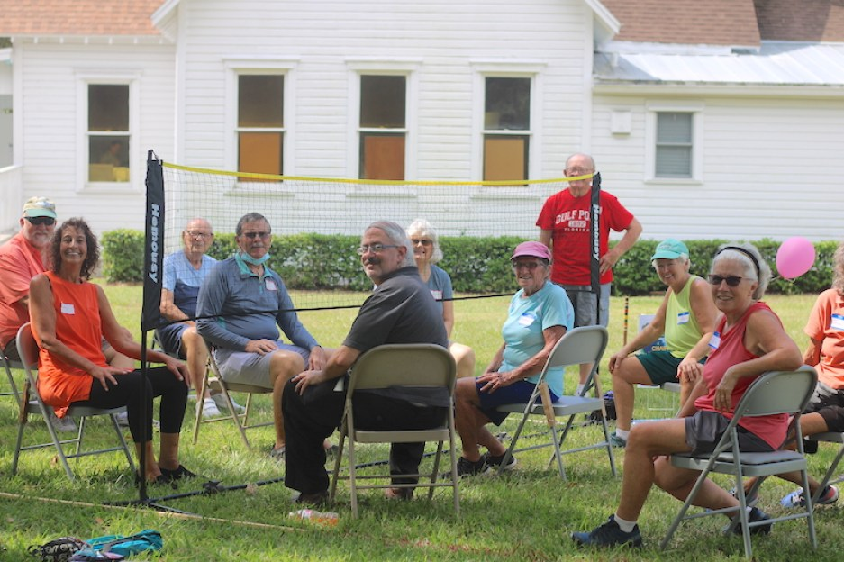 A photo of a group of people in chairs in a field on either side of a short volleyball net.