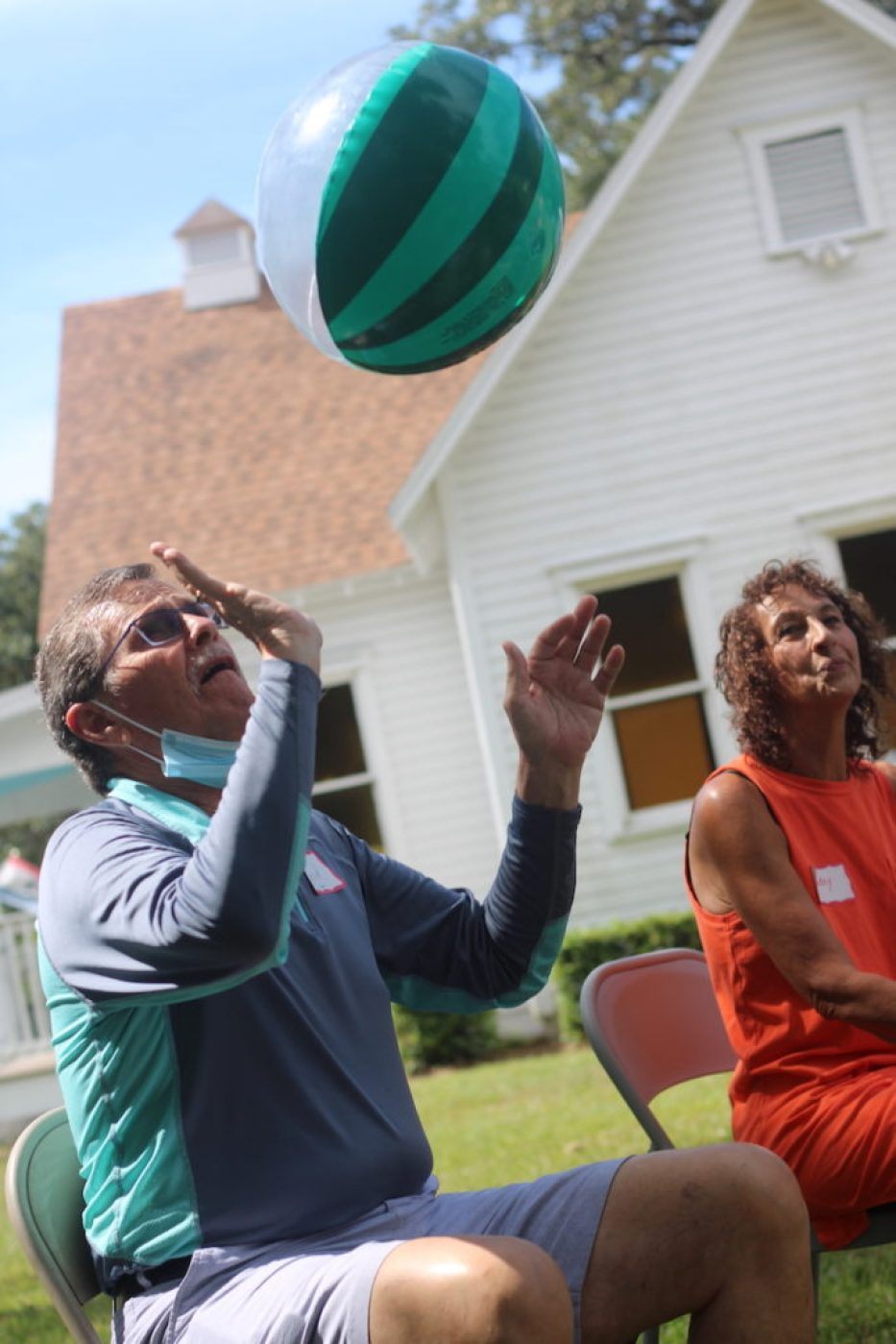 A photo of a man sitting in a chair outside tossing a ball in the air with a woman sitting next to him.
