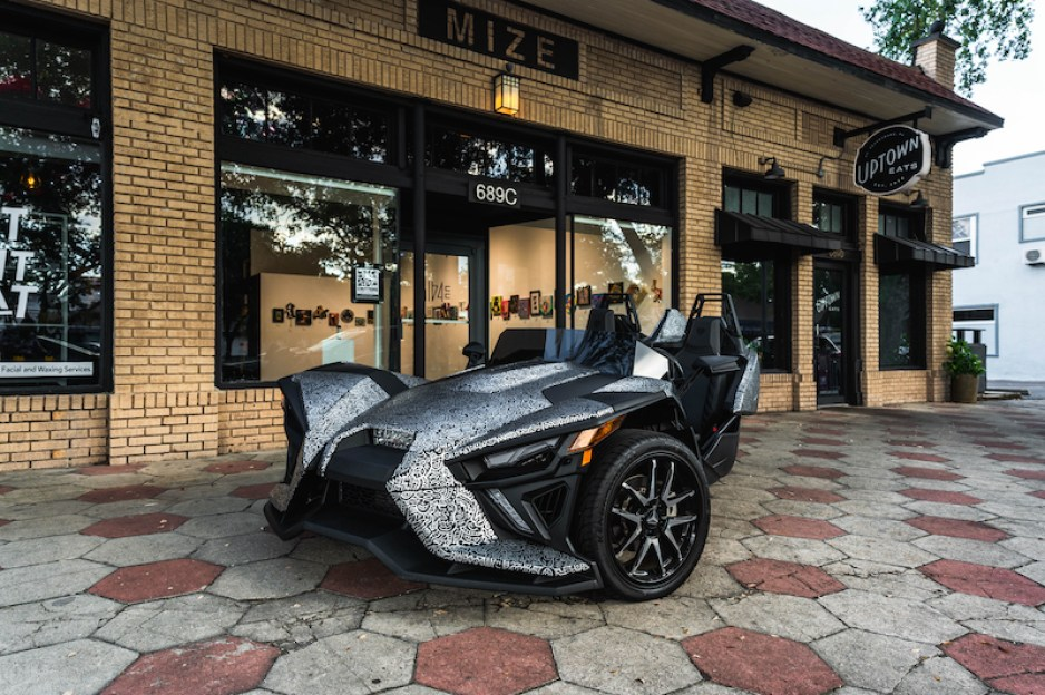 A photo of a black and gray Slingshot three-wheeled motorcycle on a hex-block sidewalk in front of a storefront.
