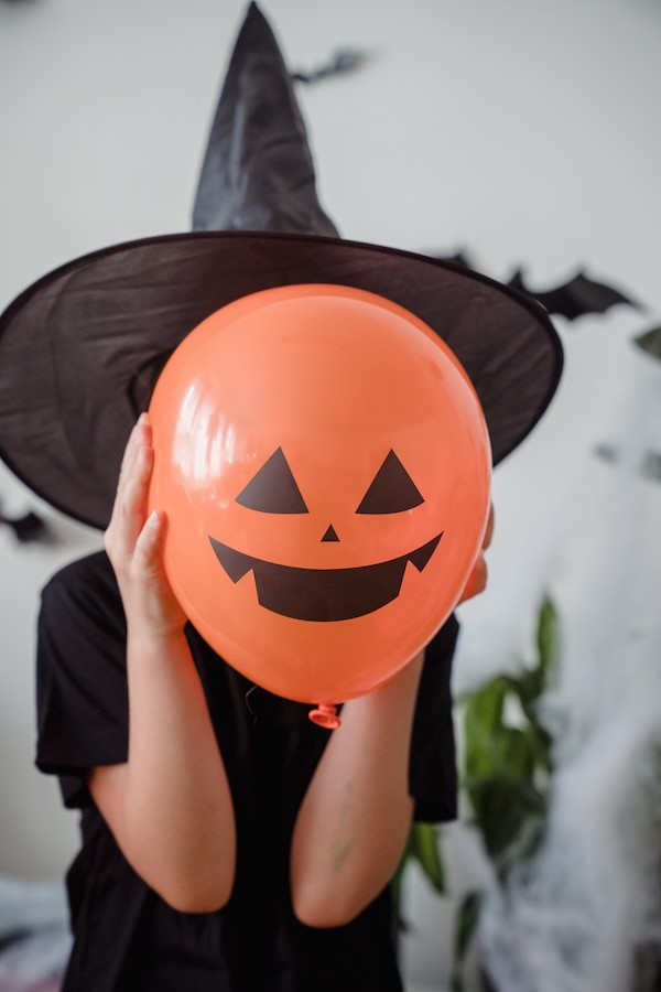 A child in a black witch hat holding up an orange balloon with a Jack-o-lantern face painted on it.
