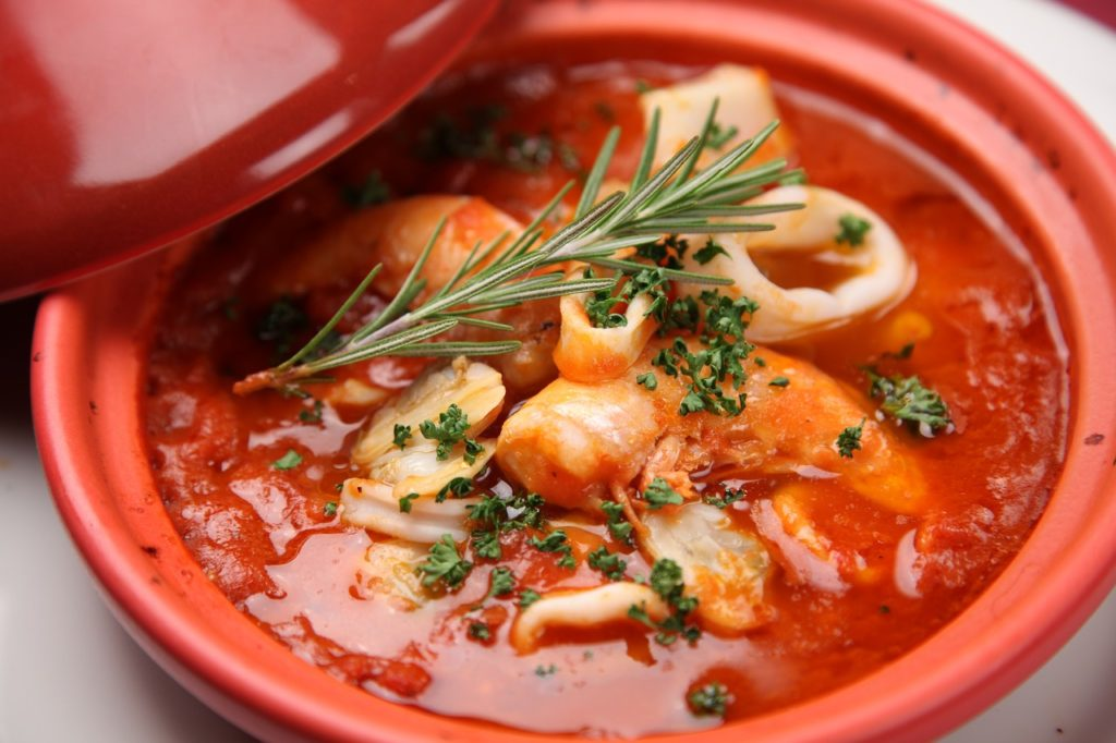 A close up photo of a seafood soup with green garnish in a red bowl.