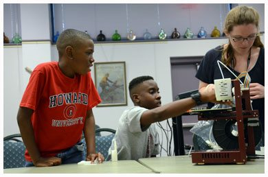 Brothers Trejan Riley, 15, and Carson Riley, 10, examine a DNA strand printed on a three dimensional printer. Trejan attends Lakewood High; his brother goes to Thurgood Marshall. Both participate in Gulfport's summer reading program at the library.