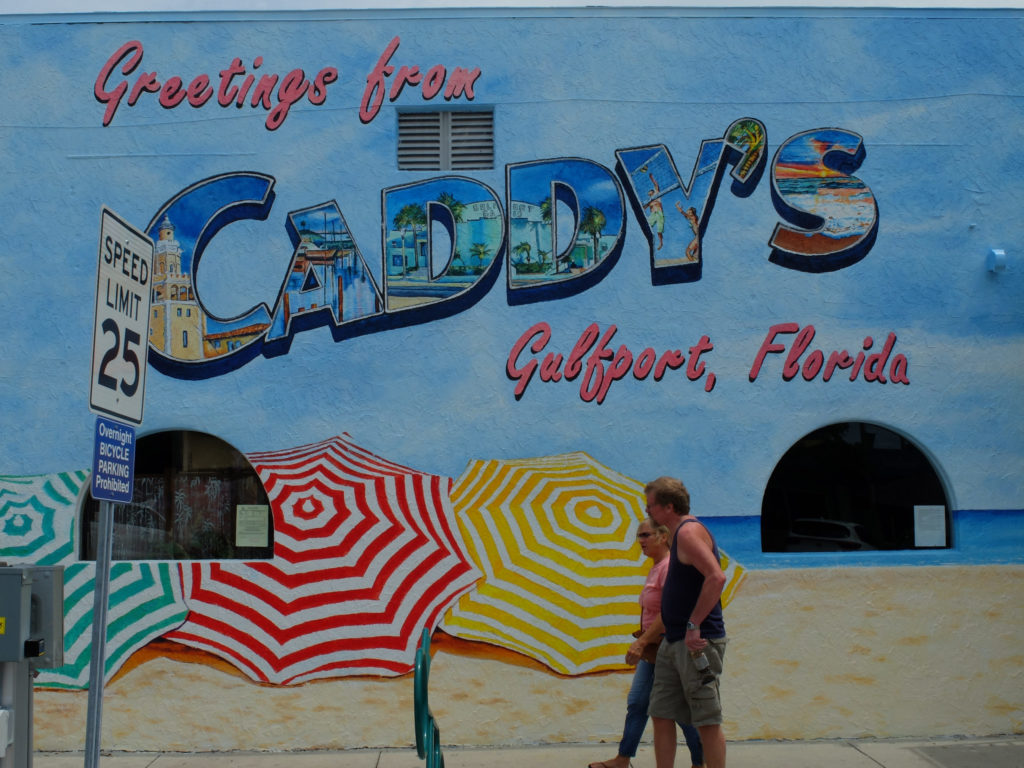 People walk past the Caddy's mural in Gulfport, Florida