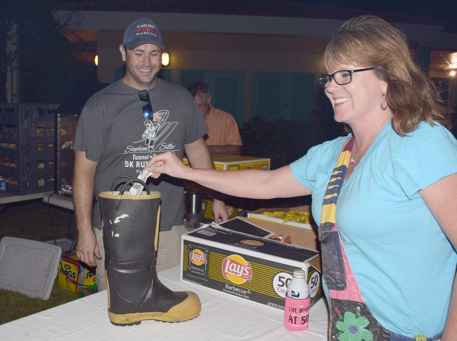 """Kelly Paradis of Largo drops some cash into a boot used to collect money at a fundraising food concession run by the St. Pete Beach Fire Department at Saturday's concert as her son, firefighter Jason Wing, looks on. """"We have been busy,"""" Wing said. """"We were a little concerned at first [because of the weather] but it turned out to be a good showing."""""""