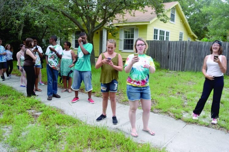 """Participants in the Gulfport Library's Teens and Tweens Summer Programs prepare to play Pokémon Go during the final party Tuesday August 2, which also included pizza, prizes and the raffling of a Kindle Fire and gift cards. Youth Services Librarian Cailey Klasson, center with tie-dyed t-shirt, said the program aims to provide a safe space for youth. """"Kids can come hang out. We cater to more than the bookish kids,"""" she said. The Pokémon Go game, which uses GPS to guide players in their search for virtual characters superimposed on the real world, has been enormously popular around the globe since its release last month."""