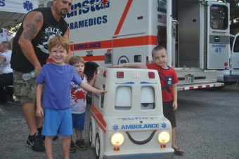 Mark Haas, 2, Duane White, 4, and Dillan Joyce, 5, hang with Sunny the Ambulance.