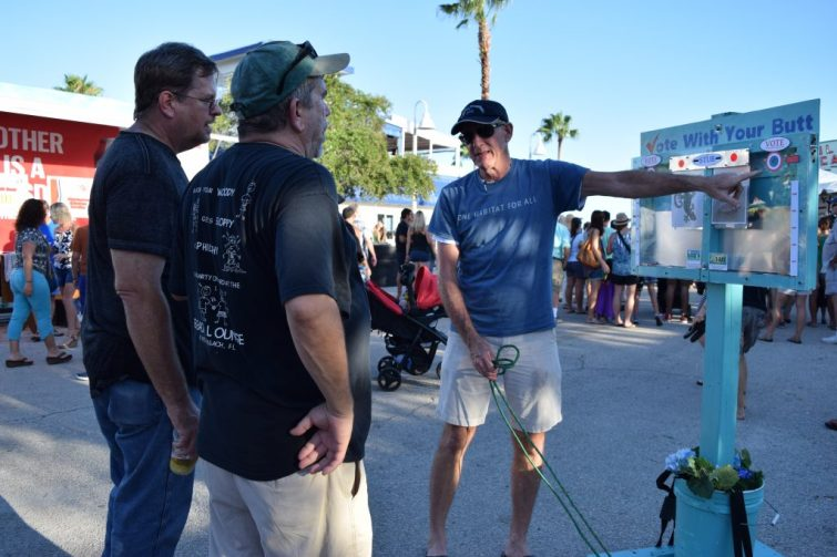 """David Westmark, co-founder of the Blue Turtle Green Bird Society environmental group with his wife Stephanie Cain, explains how the cigarette-butt """"voting"""" kiosk works to visitors at the GeckoFest in Gulfport on Saturday, September 3."""