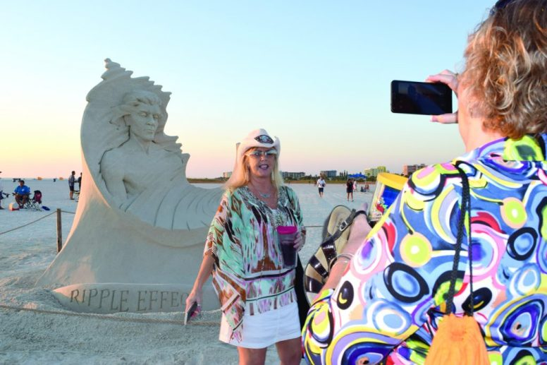 """Cindy Brown of Clearwater takes a photo of Ali Thompson, also of Clearwater, in front of a sand sculpture by artist Dan Belcher of St. Louis, titled """"Ripple Effect,"""" as the sun prepares to set Saturday November 19 in Treasure Island. The sculpture was one of 10 competing in the eighth annual Sanding Ovations Masters Cup Sand Sculpture Competition and Music Festival held November 16 through 20. First place went to a piece titled """"Biological Link"""" by Jonathan Bouchard of Montreal, who also won first place in 2012, 2013 and 2014. Brown said she's come to the contest every year since it started. Of the sculptures, she said, """"They're a little smaller this year, but very detailed."""""""