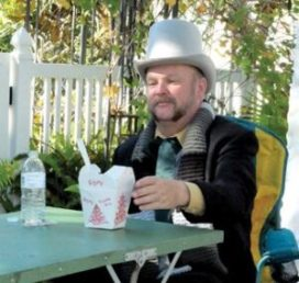 Gary Lehman, dressed as Scrooge for Gulfport's annual Holiday Hoopla, indulges in an anachronism during the day-long festival of shopping local: Chinese takeout.
