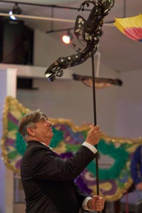 GMA board member Mike McCue holds up the gecko created by Lenne Nicklaus-Ball for bidders to view.