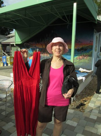 Jura Guz displays a summer-y red dress she found in the racks at the Tuesday Fresh Market Clothing Swap.