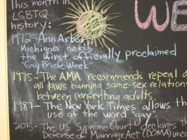 A board behind the librarians'desk is kept updated to reflect important dates in LGBTQ history.
