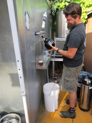 Eric Trinosky fills the first 64-ounce growler on July 1 at Peg's Cantina in Gulfport. Photo by Michael Taylor.