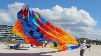A huge, colorful float-like kite being raised into the air by a much smaller man