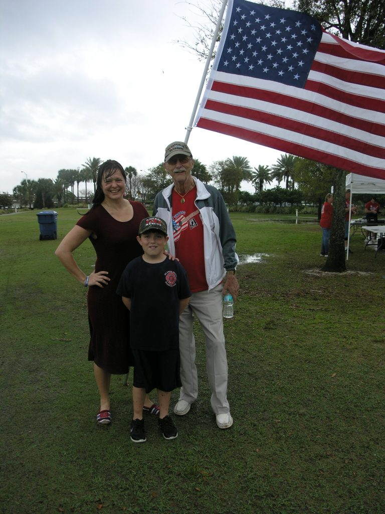 """Two veterans and a (future) firefighter: St. Pete Beach Mayor Maria Lowe, left, a veteran of the U.S. Army, poses with Korean War veteran George Stone of Seminole (Army Airborne) in front of an American flag after a rainstorm washed out a fundraising event sponsored by the Veterans of South Pinellas County in Horan Park in St. Pete Beach on Saturday, March 19. With them is Ian St. John of Lutz, 9, whose mother, Michelle St. John, is a lieutenant in the St. Pete Beach Fire Department. Asked whether he planned a military career in the future, Ian said: """"Kind of, but I'm mostly hoping to become a firefighter like my mom."""""""