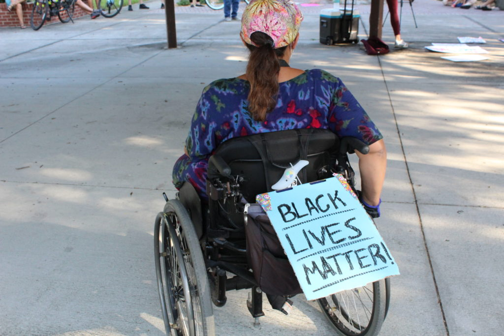 """A protestor in a wheelchair at the June 12 Black Lives Matter march in Gulfport with a """"Black Lives Matter"""" on the back of her wheelchair."""