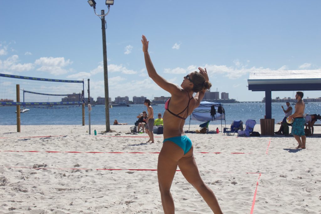Woman in blue bathing suit spiking a volleyball at the beach.