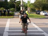 """Navarre Wigmore, 8, and his mother, Vickie Wehking, both of Gulfport, ride their bikes across Gulfport Boulevard at 52nd Street S. on their way to Gulfport Montessori Elementary School on the first day of classes. """"He was super excited,"""" Wehking said of her son. """"We got his first grade teacher again … He was so happy."""" Members of the Gulfport Fire Department, at rear left, were on hand to remind drivers to slow down now that school is back in session"""