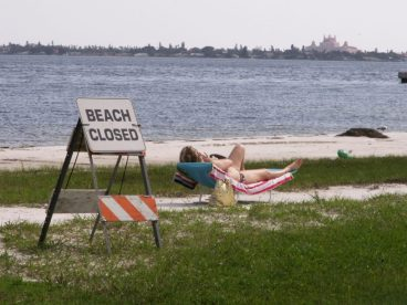 A sunbather appears unconcerned by the closing of Gulfport's municipal beach Tuesday, August 4, in the wake of heavy rains that overwhelmed area sewage systems.