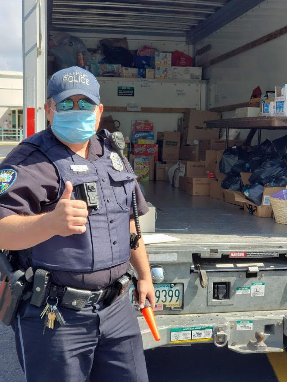 Gulfport Police Department Officer Zach Mills helps distribute food to children during the COVID-19 pandemic.