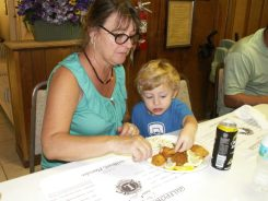 """Mary Brooks of Gulfport and her grandson Jonah, 2 ½, chow down at the Gulfport Lions Labor Day Fish Fry. """"It's one of his favorites,"""" Brooks said of her grandson. """"He's a real Florida boy."""""""