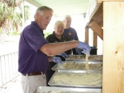 Lions Club volunteers, from left, Tom Duquette of Gulfport, Judy Galm of Sebring and Ron Coyne of Gulfport work an assembly line breading fish for the Gulfport Lions Labor Day Fish Fry.