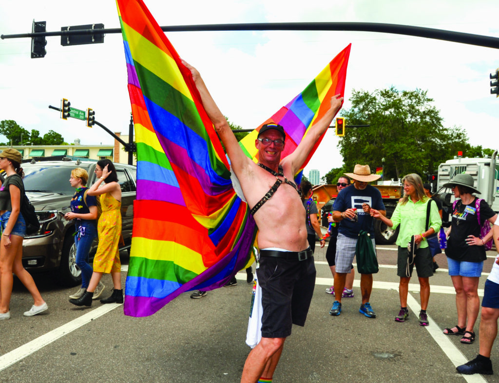 A man in black shorts and rainbow cape on the street