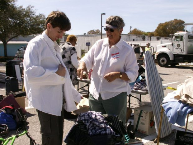 """Louis McClanahan tries on a shirt chosen by volunteer Ann Marie Anderson from a bag of clothing donated at Saturday's Junk in the Trunk at the Gulfport Neighborhood Center. McClanahan said he has picked up computers and other stuff at previous Junk in the Trunk events. """"I reuse it,'' he said. """"Try to get it to work again."""""""