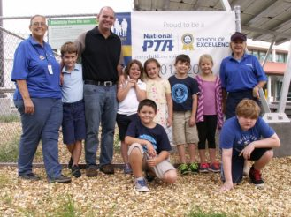 """Gulfport Montessori Elementary School students, volunteers and staff stand in front of a banner designating the school as a recipient of the """"National PTA School of Excellence"""" award. The adults are, from left, PTA President Barbara Pace, Principal James Pribble and PTA Membership Chair Rhonda Muscat."""