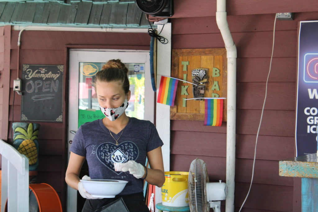 A server at the Tiki Bar & Grill wears a mask