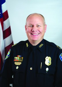 A photo of a bald man in a black police uniform smiling next to a U.S. flag.