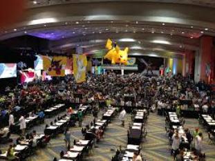 Large crowd gathers for competitive Pokémon tournament.
