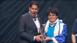 "Gonzalo ""ZeRo"" Barrios and Reggie Fils-Aime holding 2014 Invitational Trophy."